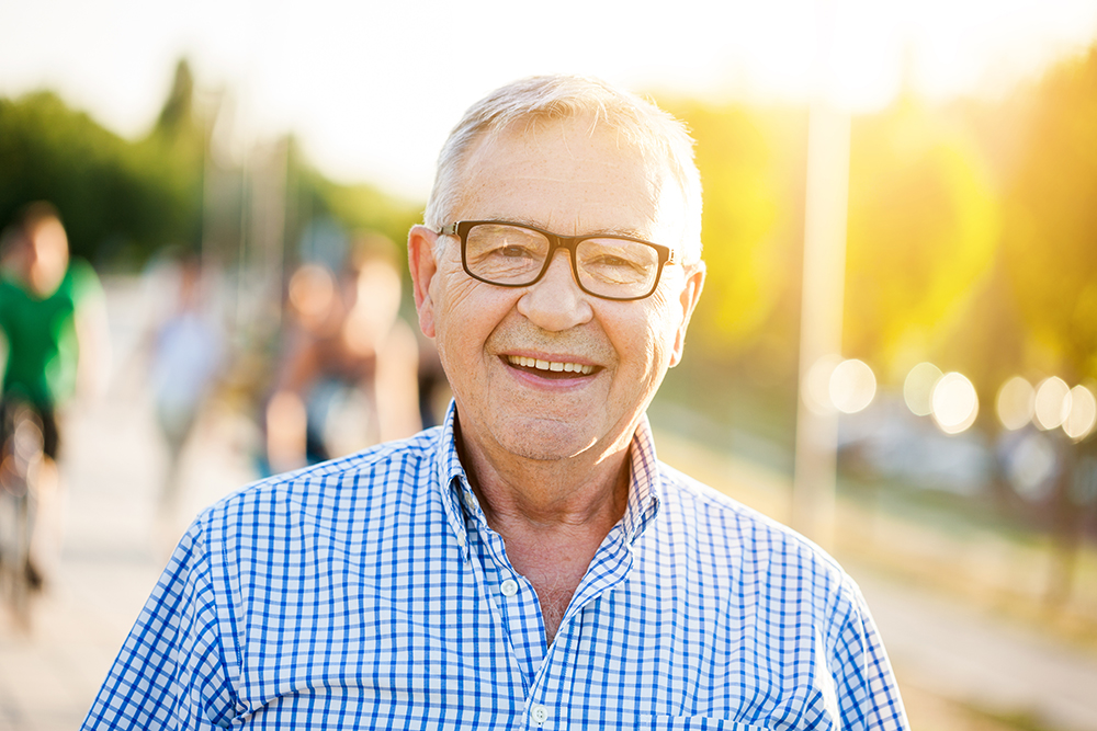Outdoor Portrait Of Happy Senior Man Who Is Looking At Camera An